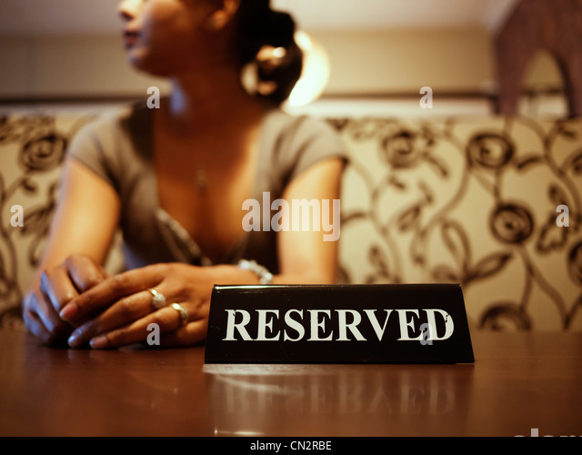 Punjabi woman waits at reserved table - Stock Image