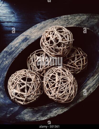 Rustic woven balls in wooden dish - Stock-Bilder