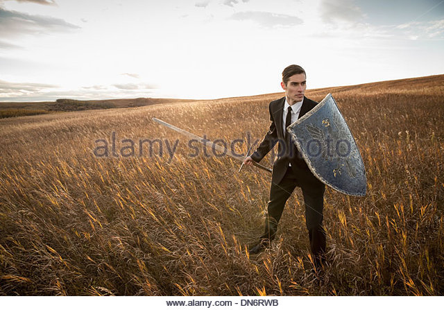 Alert businessman with sword and shield outdoors - Stock Image