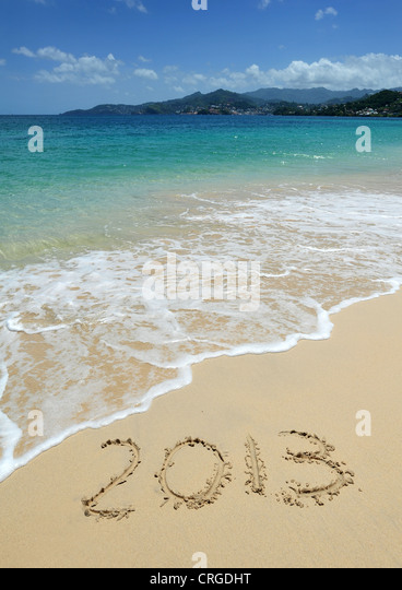 2013 written in the sand on Grand Anse Beach looking towards St George's, the capital of Grenada, West Indies. - Stock Image