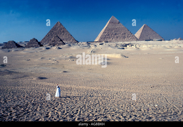 Egypt Pyramids of Giza Egyptian man dressed in white robes as size perspective - Stock Image