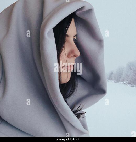 Canada, Alberta, Calgary, Profile of woman in winter scene in hooded coat - Stock Image