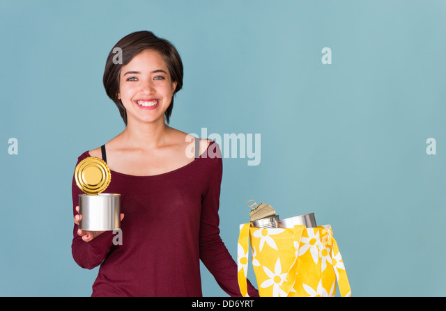 Portrait of smiling young multiracial woman recycling metal cans - Stock Image