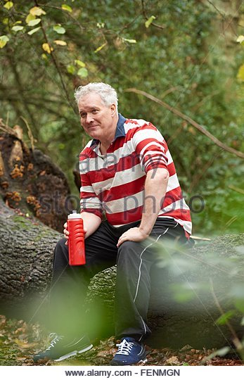 Mature male sitting on forest tree trunk drinking from water bottle - Stock-Bilder