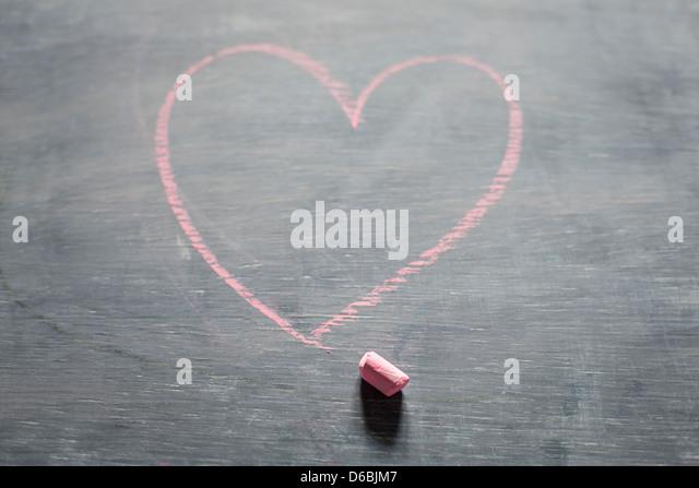 Chalk and heart shape on blackboard - Stock-Bilder