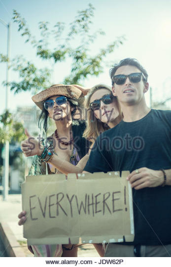 Group of friends standing by roadside holding hitchhiking sign - Stock-Bilder