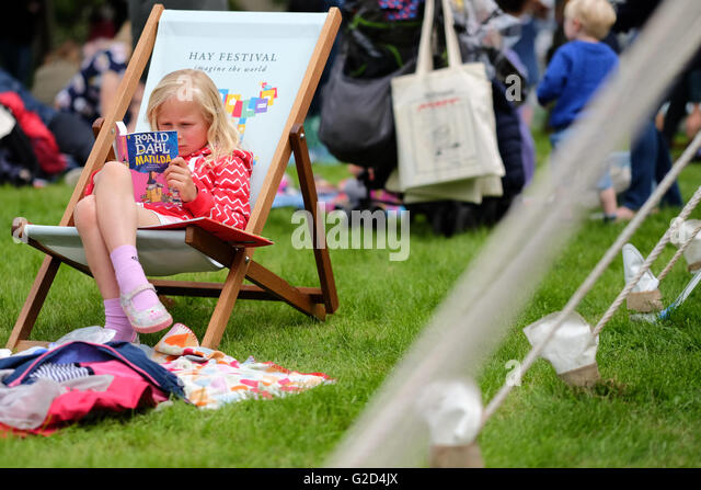 Hay Festival - Saturday 28th May 2016 - A young girl sits and reads Matilda by Roald Dahl on the Festival lawns. - Stock Image