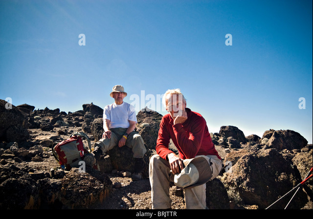 Two senior men have a rest on some small volcanic boulders after a long trek to the summit of Mt. Kilimanjaro. - Stock Image