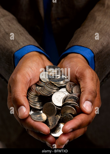 Business man with handful of coins - Stock Image