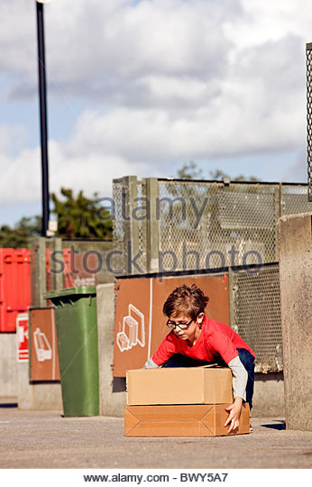 A young boy lifting cardboard boxes in a recycling center - Stock Image