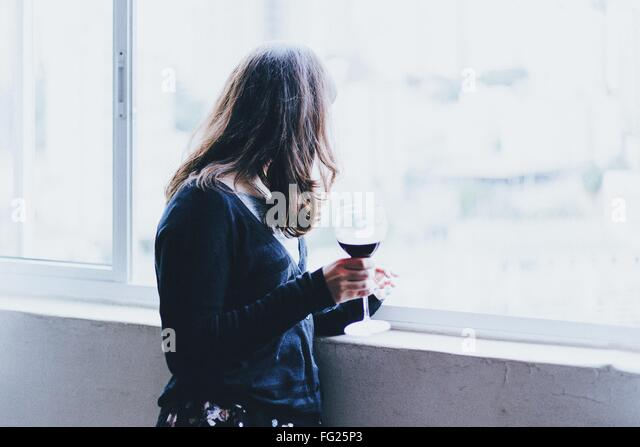 Side View Of Woman Holding Wineglass While Standing By Window - Stock Image