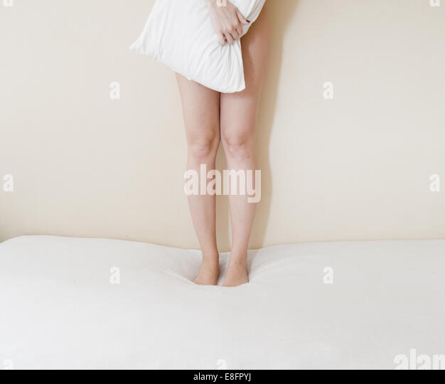 Low section of young woman standing on bed - Stock Image