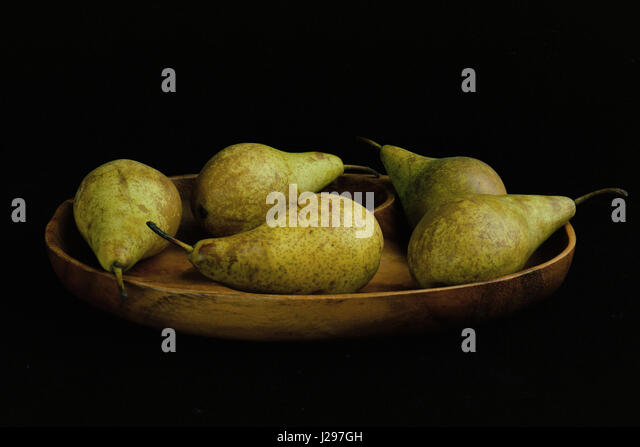 Five conference pears in wooden bowl - Stock Image