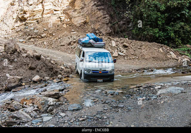 Heavily laden minivan crossing a ford in Peru - Stock Image