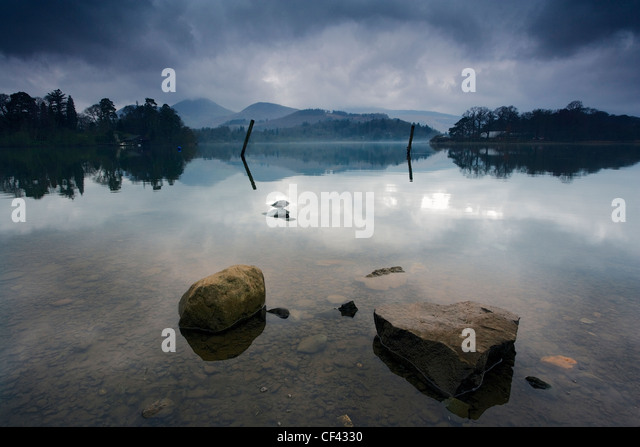 A layer of mist hovers above Lake Derwent as early morning daylight filters through a cloudy sky. - Stock Image
