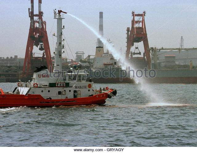 A Japanese coastguard boat sprays chemical absorbent to clean up crude oil spreading across Tokyo Bay July 3 after - Stock Image