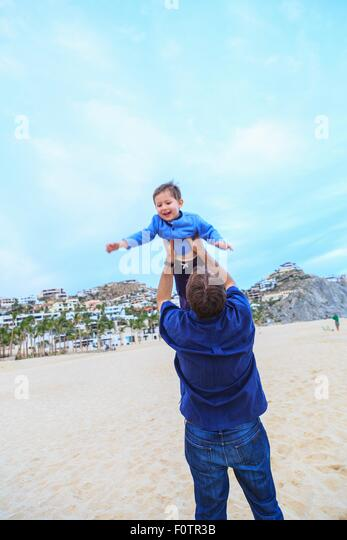 Father lifting son, on beach, rear view - Stock Image
