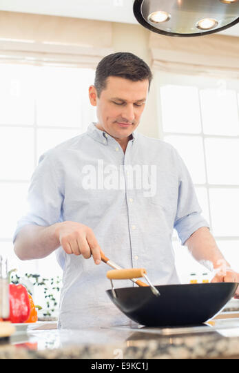 Middle-aged man cooking in kitchen - Stock Image