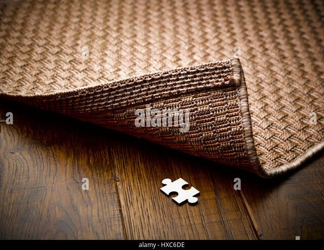 Puzzle piece hidden underneath rug - Stock Image