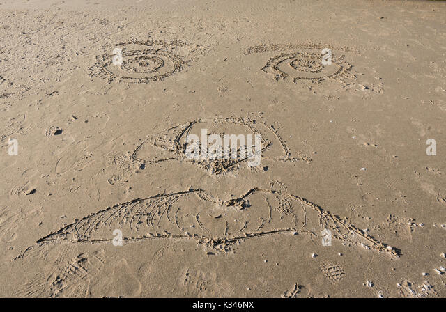 Face Carved in Sand before being washed away by the tide - Stock Image