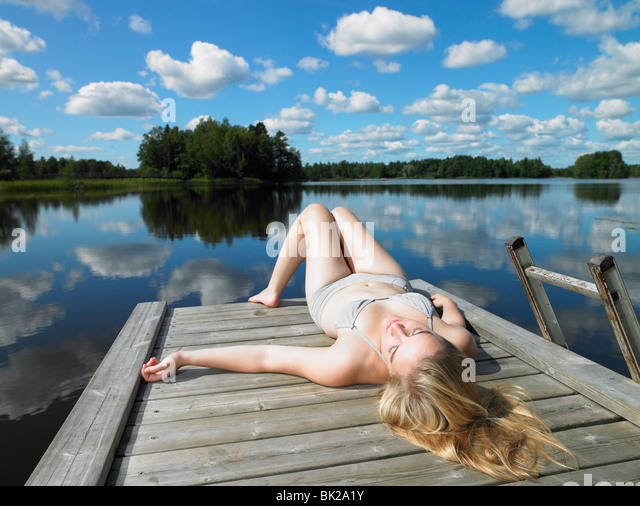 Woman tanning on a dock - Stock Image