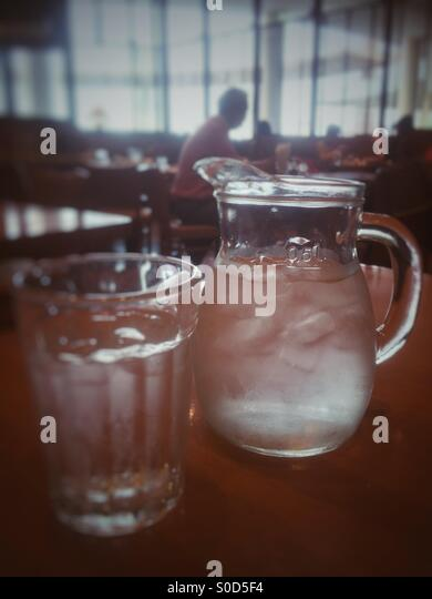 Pitcher and glass of ice water in a restaurant. Retro, faded look. - Stock Image