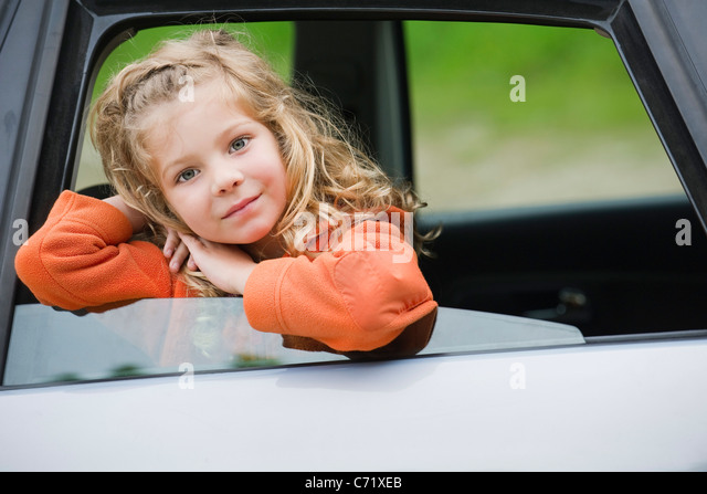 Little girl leaning out car window, portrait - Stock Image