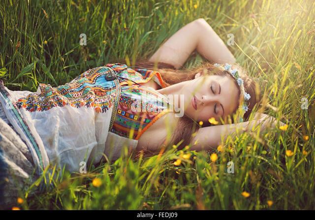 Beautiful hippie woman peacefully sleep in spring meadow - Stock Image