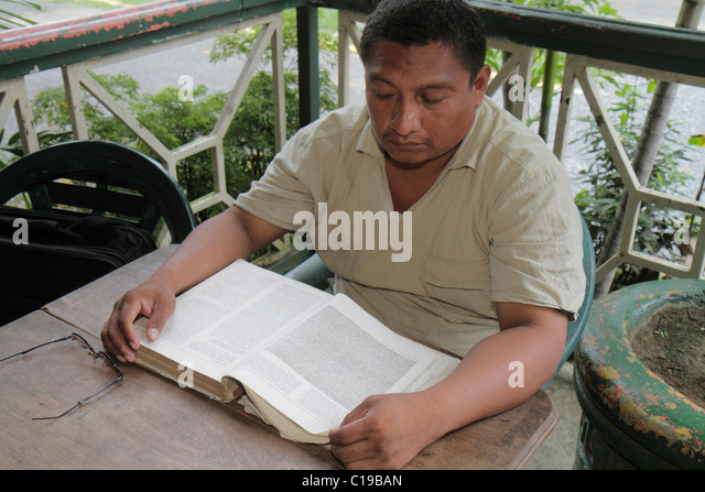 Panama City Panama Balboa Hispanic man reading balcony chair indigenous book learn education literature knowledge - Stock Image