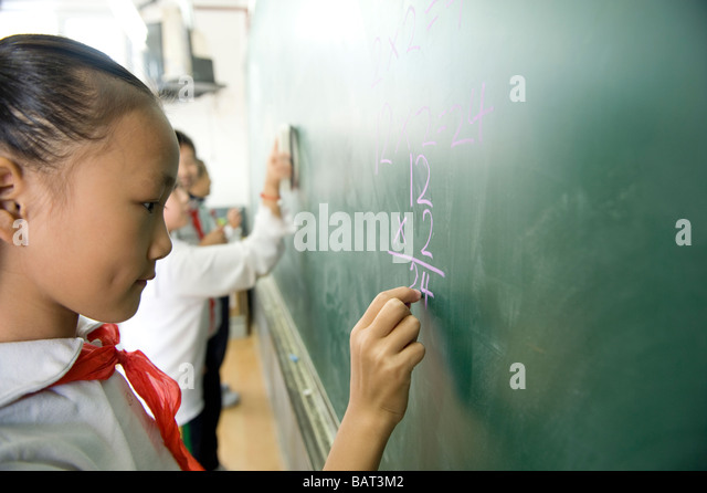 Young student practicing math on a chalkboard. - Stock-Bilder