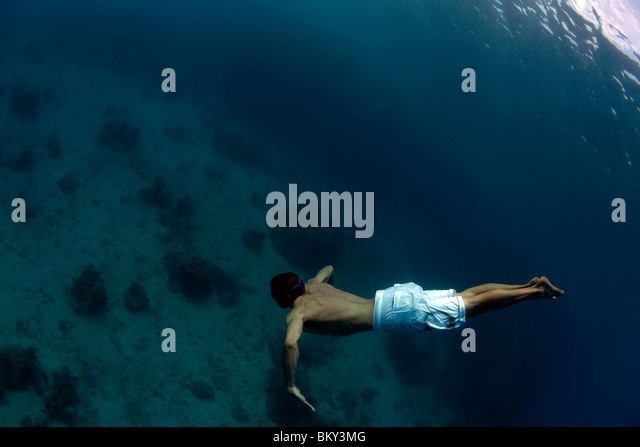 Underwater view of a man swimming deep into the tropical waters off Mana Island, Fiji. - Stock Image