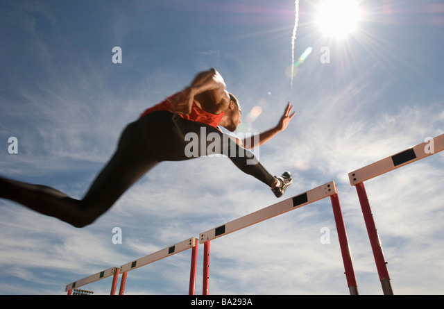 Runner jumping over running hurdle, low angle view - Stock Image