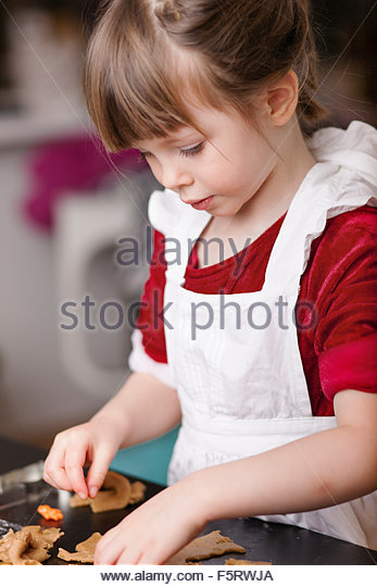 Sweden, Girl (4-5) making gingerbread cookies - Stock Image