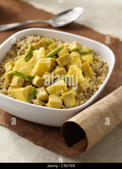 Macadamia pineapple curry over brown rice in a white bowl - Stock Image