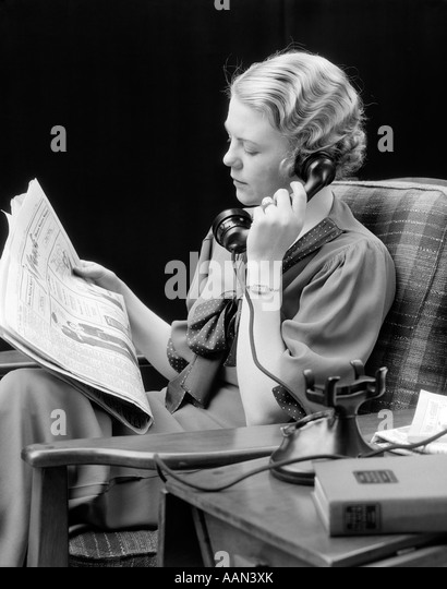 1920s 1930s YOUNG WOMAN SITTING IN CHAIR LOOKING AT NEWSPAPER TALKING ON TELEPHONE - Stock Image
