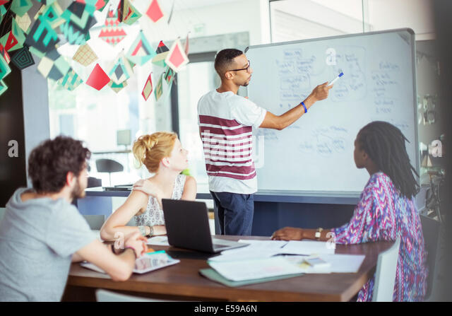 Man drawing on white board for colleagues - Stock Image