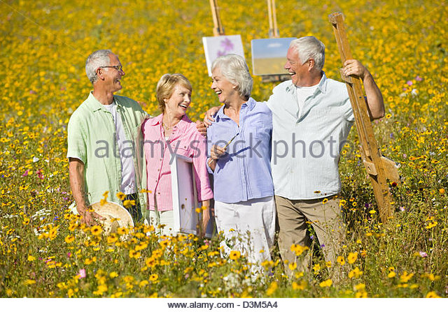 Smiling couples with paintings and easels among wildflowers in sunny meadow - Stock-Bilder