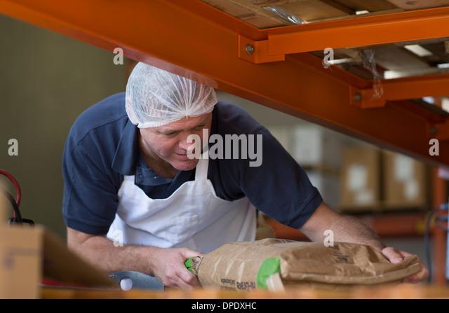 Factory worker handling parcel - Stock Image