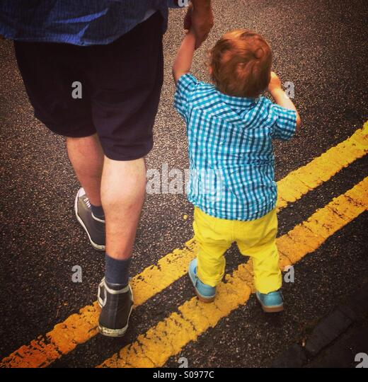 Father and son walking across double yellow lines on a road in London. - Stock-Bilder