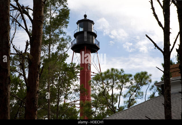The lantern room and upper structure of Crooked River Light aka Carrabelle Light viewed through the pines against - Stock Image