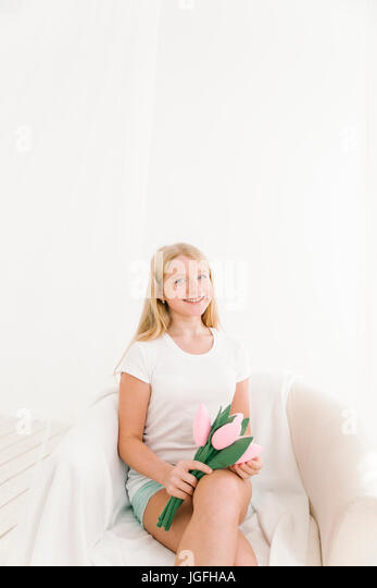 Portrait of smiling Middle Eastern girl holding toy flowers - Stock Image