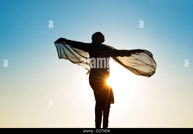Indian girl with a veil turning in the wind towards the sun. Silhouette. India - Stock Image