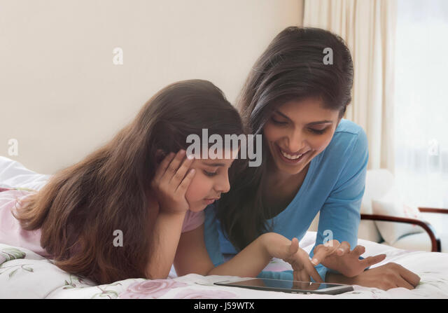 Mother and daughter using digital tablet in bed - Stock-Bilder