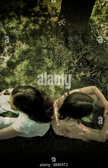 Two young girls sitting back to back under a tree - Stock-Bilder