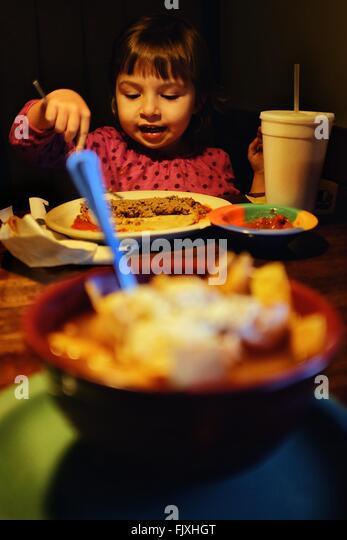 Girl Eating Food At Home - Stock Image