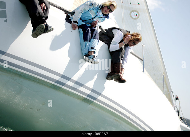 3 adults, 2 woman and 1 man leaning over the starboard side of a sailing yacht. The image is color in landscape - Stock Image