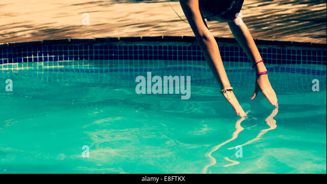 Spain, Barcelona, Girl jumping into pool in summer - Stock Image