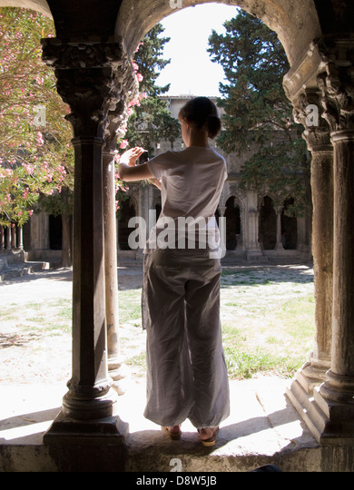 A young woman, back view, looking at a small digital camera in an archway of the cloisters of St Trophime, Arles, - Stock Image