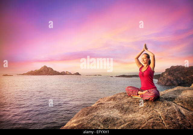 Woman doing meditation in red costume on the stone near the ocean in Gokarna, Karnataka, India - Stock-Bilder