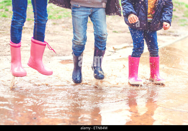Low section of three children in wellington boots jumping in a puddle - Stock Image